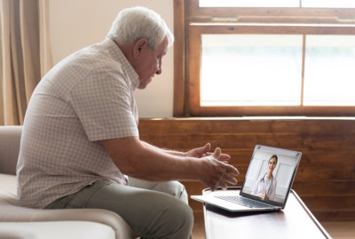 elder man talking to his doctor online