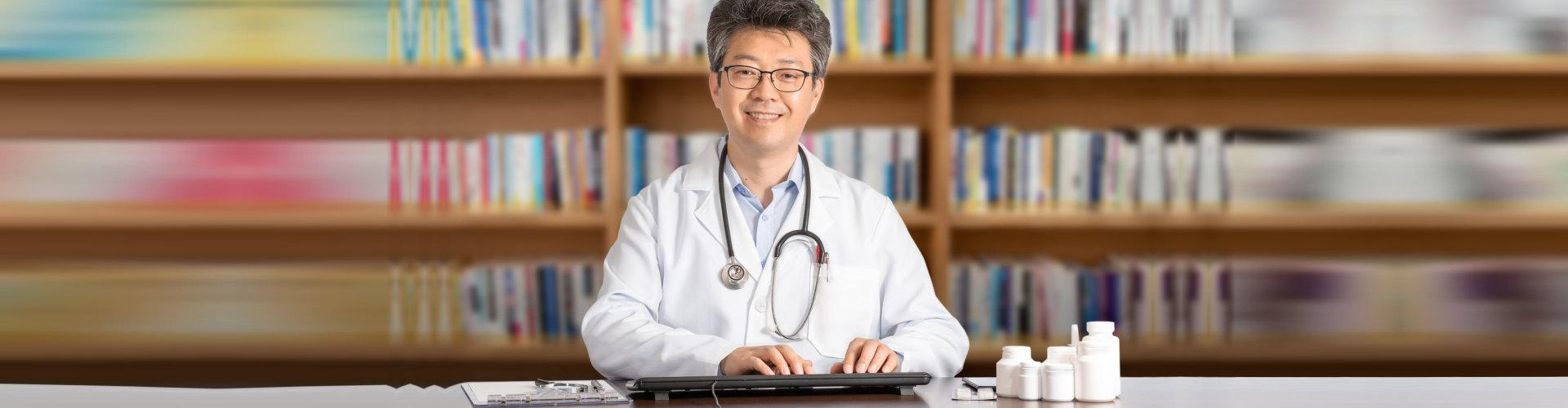 happy doctor using his desktop computer