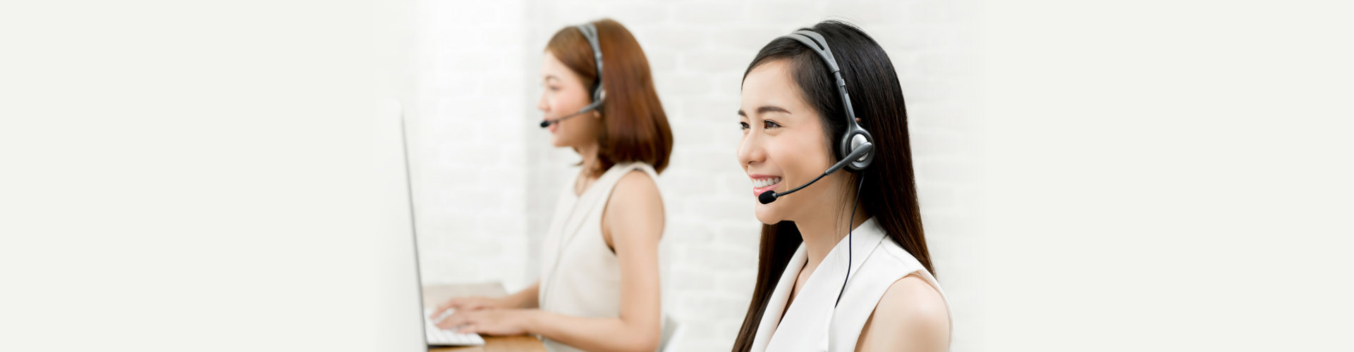 Smiling Asian woman telemarketing customer service agent team